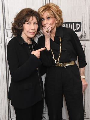 Jane Fonda coyly covered her chin while posing for photos with 'Grace & Frankie' co-star Lily Tomlin Monday.
