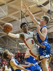 Bosse's Mekhi Lairy (2) drives past Greensburg's Kyle Sellers (34) and Mason McLeod (10) to the net during game one of the IHSAA Class 3A Regional Tournament at Memorial Gym in Huntingburg, Ind., Saturday, March 10, 2018. The Bulldogs defeated the Pirates, 75-58, to advance to the evening's Regional Championship game.