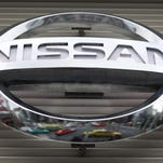 In this 2012 file photo, vehicles are reflected on the logo of the Nissan Motors Co. at a showroom in Tokyo's Ginza shopping district. Nissan announced Friday that it is recalling nearly 930,000 Altima midsize cars worldwide, some for a third time, to fix a latch problem that could let the hood fly open while the cars are moving. The new recall covers cars from the 2013 to 2015 model years including 846,000 in the U.S. that were made at factories in Smyrna, and Canton, Miss.