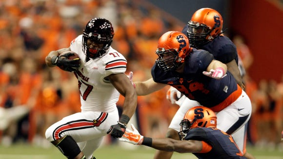 Louisville?s L.J. Scott, left, gets past Syracuse?s Ryan Sloan, top right, Robert Welsh, right center, and Durell Eskridge, bottom right, in the first quarter of an NCAA college football game in Syracuse, N.Y., Friday, Oct. 3, 2014. (AP Photo/Nick Lisi)