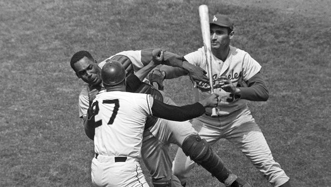 San Francisco Giants pitcher Juan Marichal (27) swings a bat at Los Angeles Dodgers catcher John Roseboro as Dodgers pitcher Sandy Koufax, right, tries to break it up during the third inning of a baseball game on Aug. 22, 1965 at Candlestick Park.