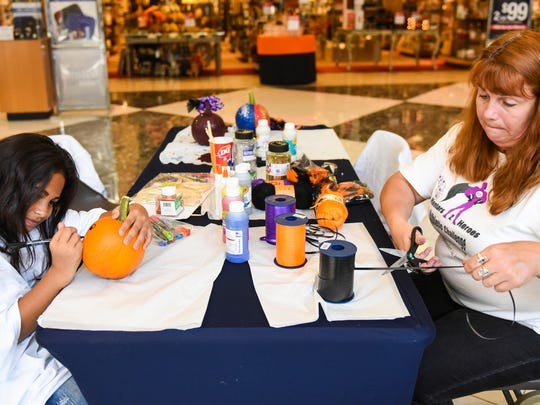 Laura Quick (right), of Mentors 2 Heroes, helps Samantha Ortiz, 8, of Hershey decorate a pumpkin at a Mentors 2 Heroes fundraiser at the Lebanon Valley Mall on Saturday, Oct. 15, 2016.