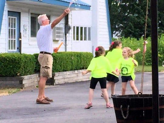 Crush driver Bill Harris entertains some children as