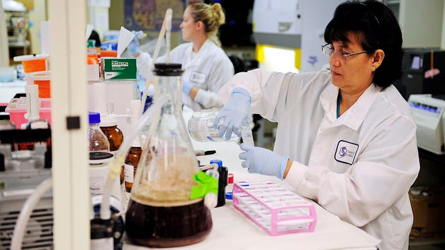 FILE - In this November 2012 file photo, Arlene Ignacia, a medical technician, prepares cell samples to separate white and red blood cells in a centrifuge machine at the NeoGenomics facility in Fort Myers, Fla.