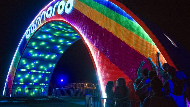Festivalgoers remove small pieces of plastic off the Bonnaroo arch to have a keepsake during the final day of Bonnaroo 2015.