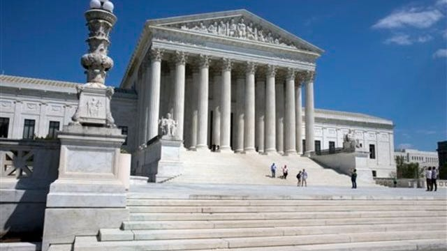 People walk on the steps of the U.S. Supreme Court.