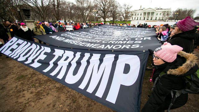 Participants of the Women's March hold banners near the White House, Saturday, in Washington, three years after the first march in 2017, the day after President Donald Trump was sworn into office.