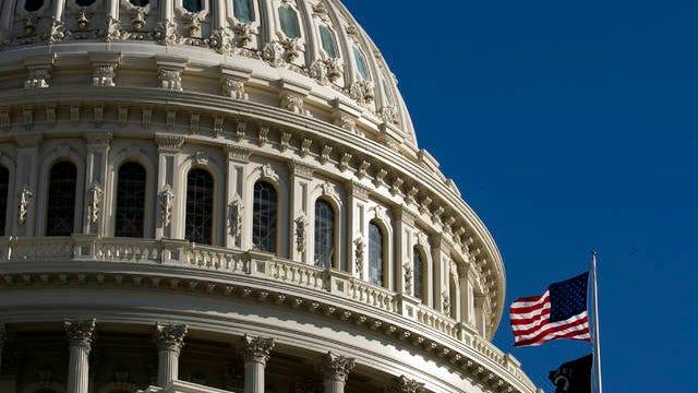 The U.S. flag flies over the U.S. Capitol in Washington, Sunday.