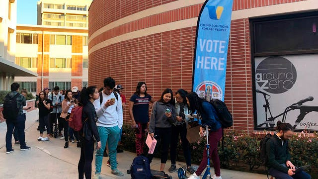 People wait in line to vote at a polling station at the University of Southern California in Los Angeles.