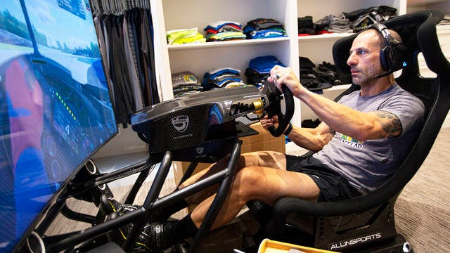 IndyCar driver Tony Kanaan, of Brazil, practices on his racing simulator in his home in Indianapolis on March 28. Kanaan, along with other IndyCar drivers and NASCAR's Jimmie Johnson will compete in the series' inaugural virtual racing event Saturday.