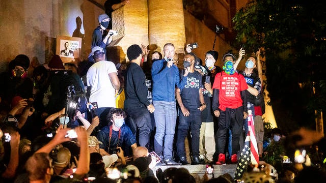 Portland Mayor Ted Wheeler speaks to Black Lives Matter protesters on Wednesday in Portland, Ore. Late Wednesday Wheeler joined protesters at the front of the crowd and was hit with chemical irritants several times by federal officers dispersing demonstrators.