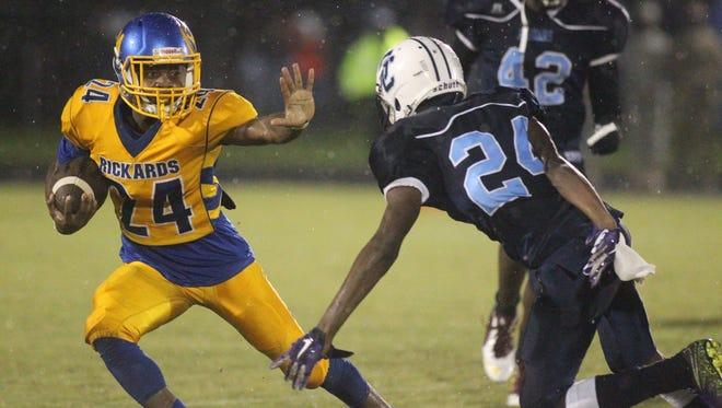 Rickards running back Tyrese Thornton prepares to stiff-arm a Gadsden County defender.