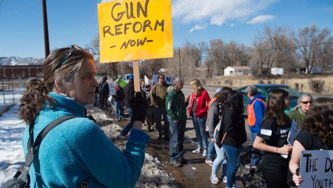 Margaret Francia stands on Laporte Avenue as high school students walk to Old Town Square for a rally voicing concerns about school safety on Tuesday, February 27, 2018. Francia said she was there to support students and start a conversation about sensible gun reform.