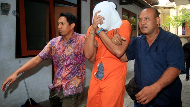 Indonesian police officers escort a concealed Tommy Schaefe  to a hospital for medical check.