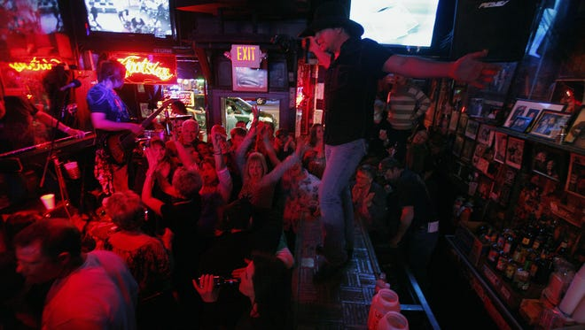Chillicothe native Scott Collier (middle) of the Scott Collier Band performs on the bar to a full crowd in Tootsie's Orchid Lounge in this 2010 file photo. Collier will return to Chillicothe to play this weekend's Salt Creek Valley Festival.