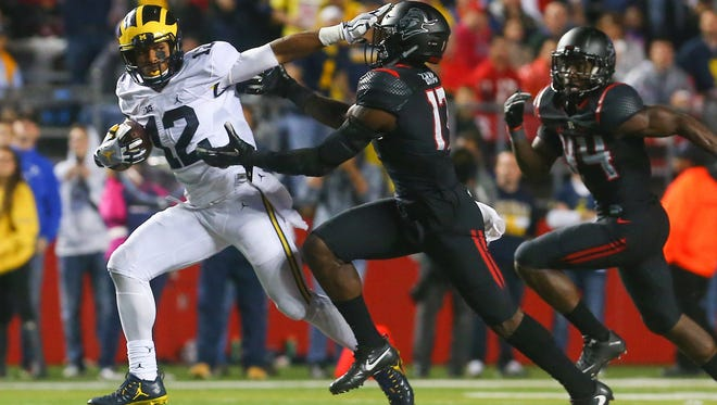 Michigan Wolverines running back Chris Evans (12) runs with the ball while avoiding a tackle attempt by Rutgers Scarlet Knights defensive back K.J. Gray (17) during the second half at High Points Solutions Stadium.