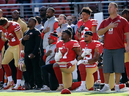San Francisco 49ers outside linebacker Eli Harold, bottom center, and safety Eric Reid, bottom right, kneel during the national anthem before an NFL football game against the Arizona Cardinals in Santa Clara, California on Nov. 5.
