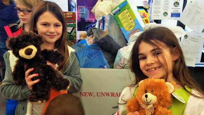 "Adeline Goeken, right, and friend Aaliyah Wilson prepare to donate teddy bears to the Fareway Toys for Tots collection box during her unique ""do good"" birthday party."