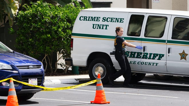 A Lee County Sheriff's Office technician works the scene of an ongoing death investigation Wednesday at The Parkway condominium complex in North Fort Myers.