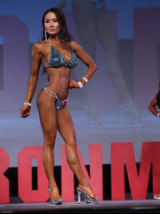 Physique by Dr. D bikini athlete, Summer Vu, executes her front bikini pose during the first call out for the novice A bikini class at prejudging in the 2017 NPC Washington Ironman.