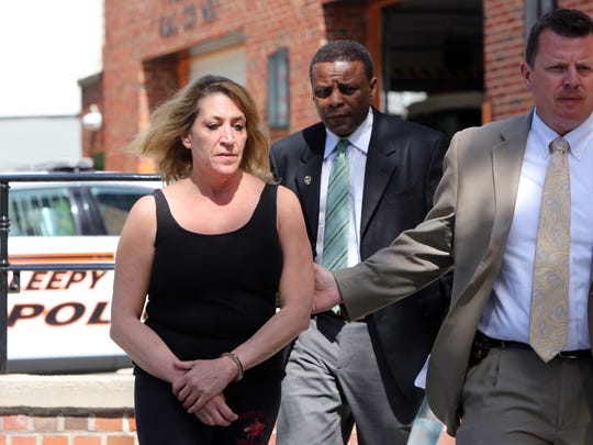 Police escort Carol Ressa after her arraignment at