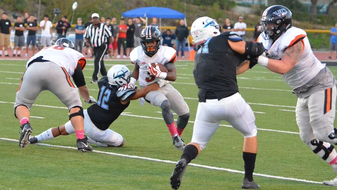 Ventura College running back Thomas Duckett attempts to break the tackle of Moorpark College's Cashius Nichols in the 50th Citrus Cup game at Griffin Stadium last year.