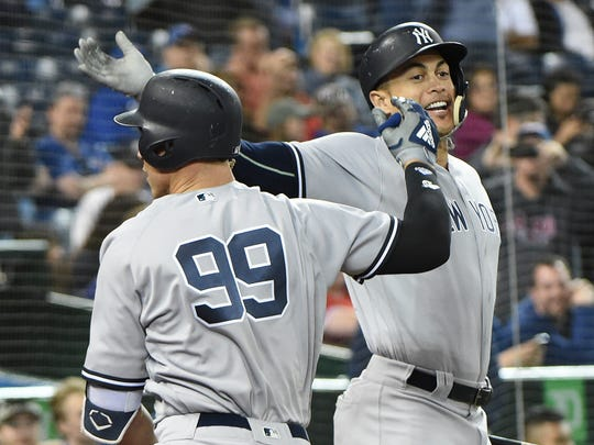 Jun 6, 2018; Toronto, Ontario, CAN;  New York Yankees right fielder Aaron Judge (99) is greeted by left fielder Giancarlo Stanton (27) after hitting a two run home run against Toronto Blue Jays in the thirteenth inning at Rogers Centre.