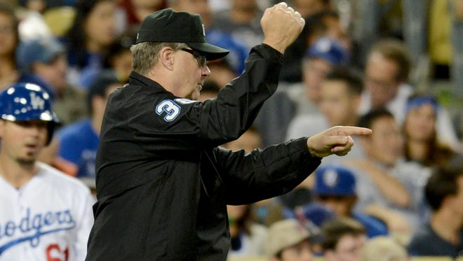 MLB umpire Gary Cederstrom signals as a review of a play is overturned in the the fourth inning of the game between the Los Angeles Dodgers and the Chicago White Sox at Dodger Stadium.