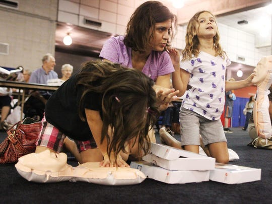 Rosanna Catalano Flury, center, teaches her daughters, Keegan, 8, and Neliana, 6, how to perform CPR at a previous Press the Chest event.