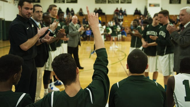 Winooski's Sean Callahan points a finger to the sky before his team's game against Milton Yellowjackets on Dec. 29, 2015 in Winooski.