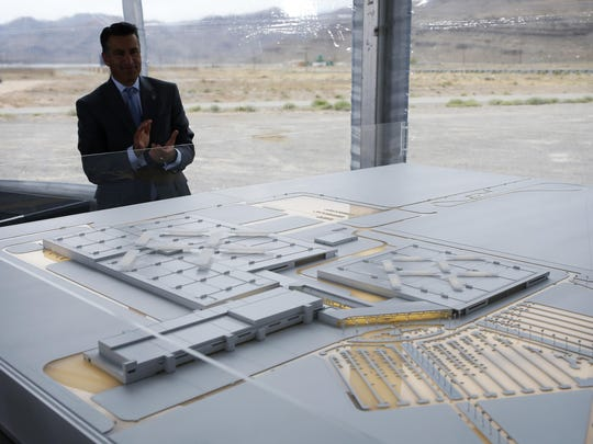 Nevada Gov. Brian Sandoval looks at a model for a Faraday Future factory, Wednesday, April 13, 2016, in North Las Vegas, Nev. The upstart electric car company held an event to mark the start of construction at a Las Vegas-area production plant toward which Nevada had pledged up to $335 million worth of incentives.