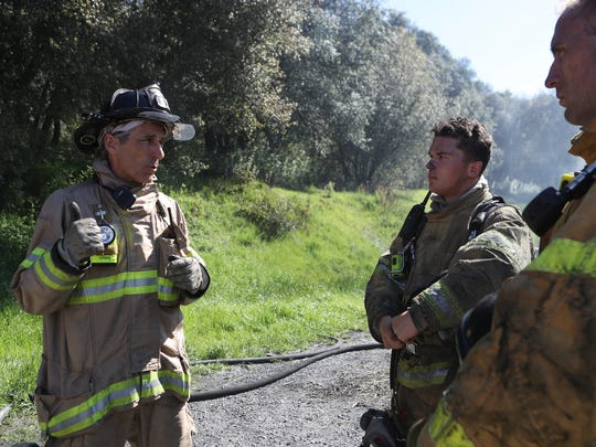 Redding Fire Engineer Jamie Harvey, from left, talks with Shasta College Fire Academy students Blaine Littleford and Mark Accinelli during training Tuesday.