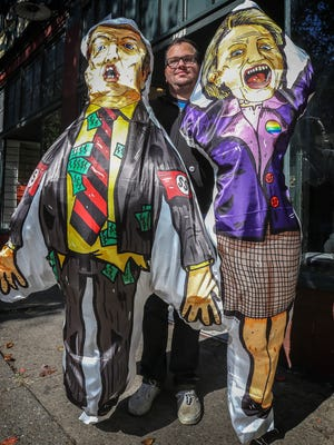 Donald Trump and Hillary Clinton voodoo dolls being held by Matt Barnes, Principal and Creative Director of Studio Post Office, on Oak Street.
