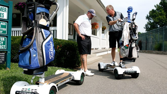 Enquirer sports strategist Jason Hoffman, left, gets a lesson about a GolfBoard from Harry Alexander, PGA golf professional at The Clovernook Country Club Monday July 25, 2016. GolfBoards, an alternative to a golf cart, can speed up pace of play, a round of golf should take about 2:30 instead of 4:40, according to golfboard.com.