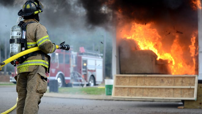 """Tim Short, a Hardin County firefighter, waits to douse the flame out on a """"room"""" not equipped with sprinklers at Hardin County High School in November of last year. The activity demonstrated the benefits of having sprinklers in the home. MEGAN SMITH/The Jackson Sun"""