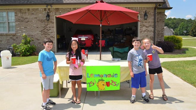 Russ and Will McGlaughn pose with friends and customers MeiLeigh Mintz and Rylee Jo Neal at their lemonade stand. In two hours Tuesday afternoon, they raised $300 and donated it to the Whorton Bend Fire Department.