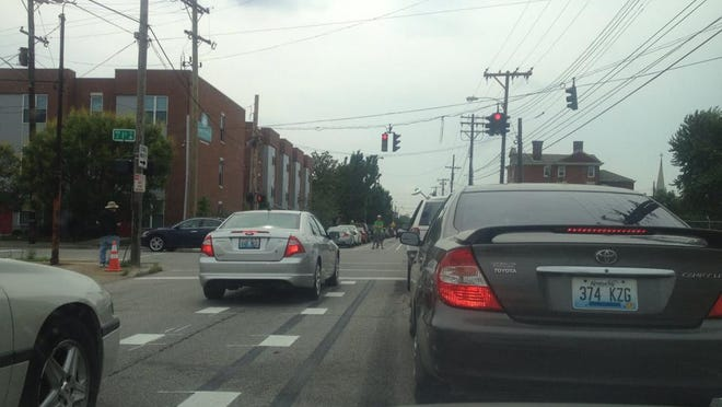 Cars driving in a new dedicated bike lane yesterday were confronted by David Morse (visible under traffic light in bike lane).