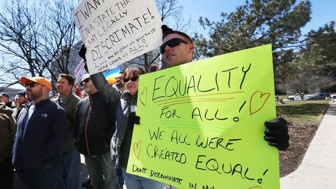 Jeremy Greenwood (right), and Colleen Gannon, both Indianapolis, held signs at the rally on the steps of the Statehouse in Indianapolis, where several thousand opponents of Indiana's recently passed Religious Freedom Restoration Act (RFRA) held a rally on Saturday, March 28, 2015.