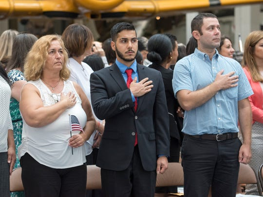 Oya Aydan, of Turkey, left to right, Alireza Bahadorkhan, of Iran, and Oleg Balan, of Moldova, stand for the National Anthem during the naturalization ceremony at the National Naval Aviation Museum in Pensacola on Friday, July 21, 2017.  130 people from 52 countries became United States citizens.