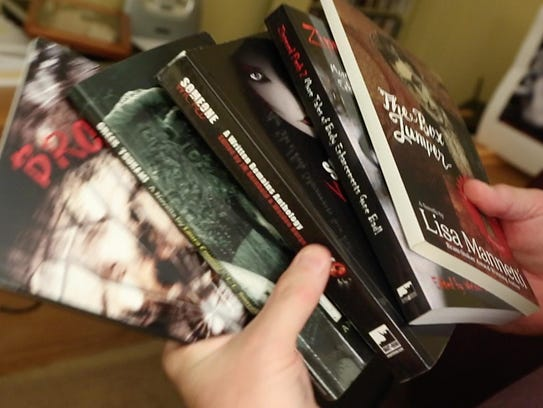 Weldon Burge thumbs through some titles published by