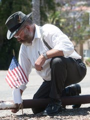Steve Schleder ties an American flag into place to mark the grave of a US military veteran buried under the parking lot of what is now Cemetery Memorial Park in Ventura. Schleder was placing flags on the graves of veterans buried at the site in preparation for Monday's Memorial Day ceremony at the park.