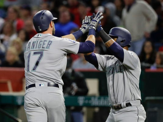 Seattle Mariners' Mitch Haniger, left, celebrates his two-run home run with Jean Segura during the first inning of a baseball game against the Los Angeles Angels on Saturday, April 8, 2017, in Anaheim, Calif. (AP Photo/Jae C. Hong)