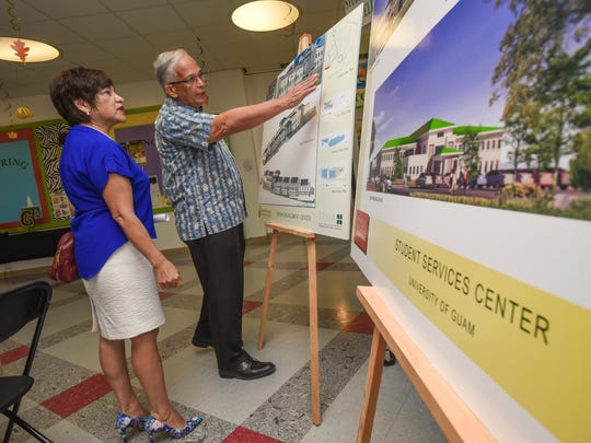 In this Dec. 6, 2016, file photo, University of Guam President Robert Underwood, right, describes to Judith Won Pat, the plans to construct buildings to house the School of Engineering and the Student Services Center at the Mangilao campus.