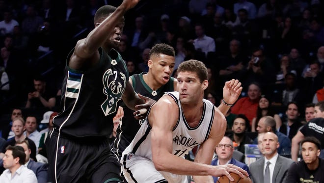 Milwaukee Bucks' Thon Maker, left and Giannis Antetokounmpo defend Nets' Brook Lopez (11) during a game Wednesday, Feb. 15, 2017, in New York. The Bucks won 129-125. Lopez scored a season-high 36 points and tied his career high with eight blocks for the Nets.