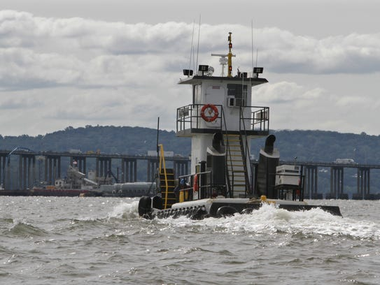 A construction tugboat is seen creating a wake in shallow