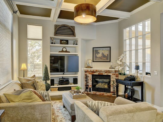 The dramatic coffered ceiling of the great room is just one of the upgrades added by the current homeowners of 641 Camino de la Luz. There are also a used-brick fireplace, built-in entertainment center and large window that looks out to the backyard.