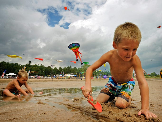 Cooper Anderson, 6, front, and brother Fisher Anderson, 4, both of De Pere, play in the sand during the annual Kites Over Lake Michigan event on Saturday, Aug. 30, 2014 at Neshotah Beach in Two Rivers. Matthew Apgar/HTR Media