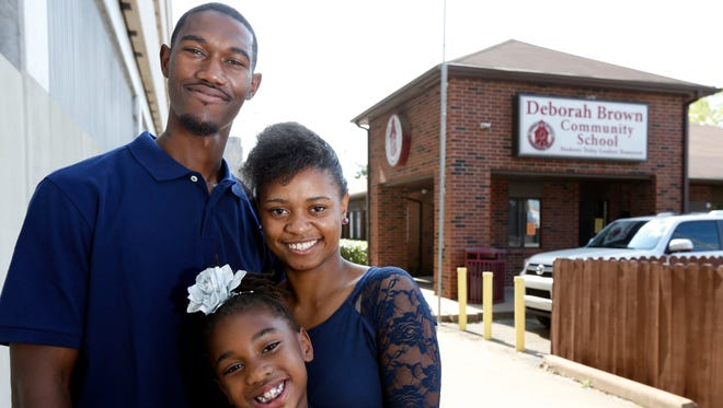 In this Sunday, Sept. 8 photo, Terrance Parker, left, poses with wife Miranda Parker, right, and their daughter Tiana, 7, in front of Deborah Brown Community School in Tulsa, Okla.