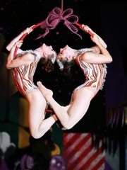 """Acrobats swing suspended in midair as a part of Cirque Dreams """"Holidaze,"""" a winter wonderland variety show."""