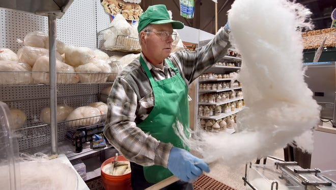 """Larry Hamilton of Potter County, pulls together some maple cotton candy at the PA Maple Syrup Producers Council stand in the food court last week. The show continues through Saturday. Hamilton, who has been making the cotton candy at the Pa. Farm Show for the past 30 years at the stand, credits his upbringing for his passion of maple syrup. """"We got sap in our boots at a very young age, and it kinda stuck,"""" jokes Hamilton."""